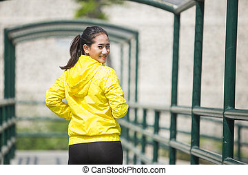 Young asian woman exercising outdoor in yellow neon jacket