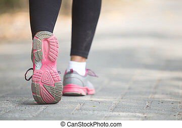 close up of running shoes - close up portrait of woman...