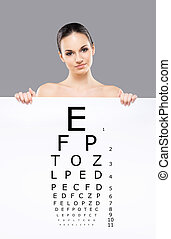 Attractive woman with a banner of test vision table over...