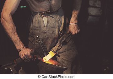 Smithy - Blacksmith working metal with hammer on the anvil...