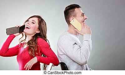 Young happy couple talking on mobile phones. - Young couple...