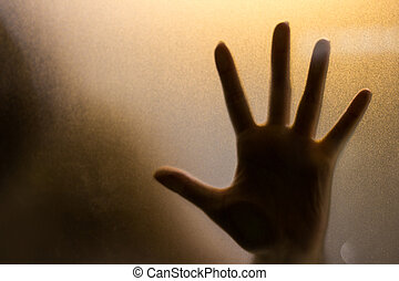 Shadow of hand behind wet glass, close-up