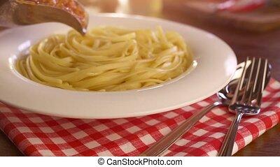 Pouring sauce onto spaghetti
