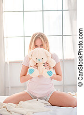 Woman sitting with teddy bear on the bed - Portrait of a...