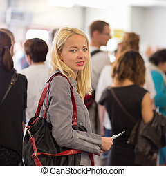 Young blond caucsian woman waiting in line - Young blond...