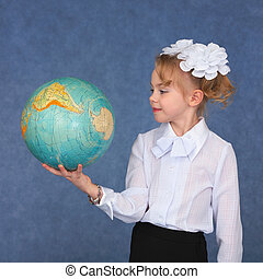 Schoolgirl looking at a geographical globe on a blue...