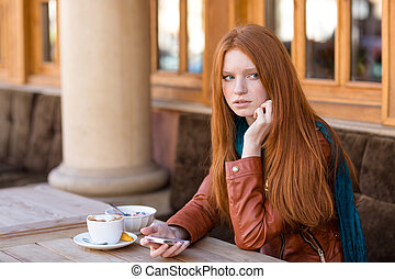 Woman using cellphone and waiting for somebody in outdoor...