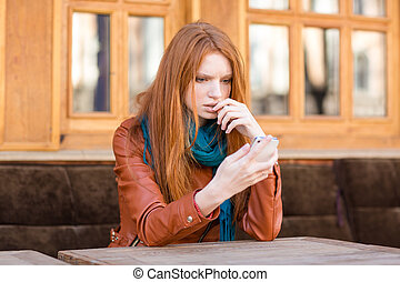 Embarrassed shoked lady reading message in mobile phone -...