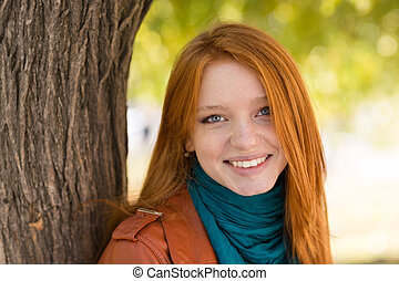 Young cheerful attractive woman standing near the tree in...