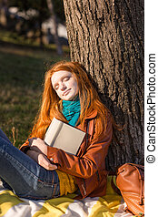 Beautiful redhead lady sleeping under the tree in park -...