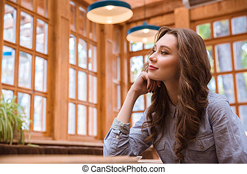 Thoughtful woman sitting in cafe - Portrait of a thoughtful...