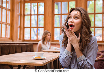 Cheerful woman talking on the phone in cafe - Portrait of a...