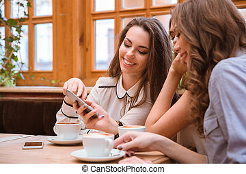 Women using smartphone in cafe - Portrait of a smiling three...