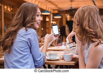 Woman showing something on smartphone screen to her...