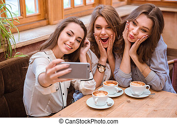 Three women making selfie photo in cafe - Portrait of a...