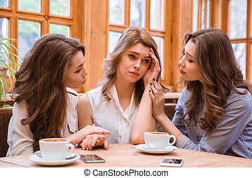 Two women comforting crying girl in cafe - Portrait of a two...