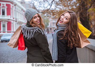 Two women walking with shopping bags outdoors - Portrait of...