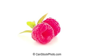 Ripe raspberry with leaf isolated on white background.