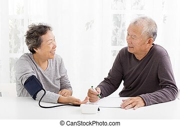 happy Senior couple taking  blood pressure in living room