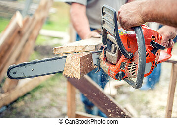industrial workers cutting timber wood with chainsaw. Men sawing using electrical chainsaw