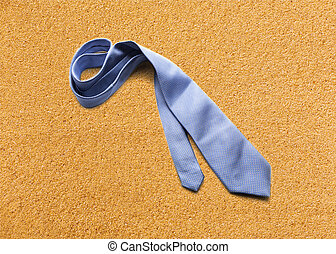 Blue necktie on sand