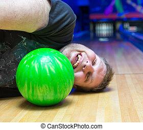 Drunk man on bowling alley - Bizarre drunk man lying on...