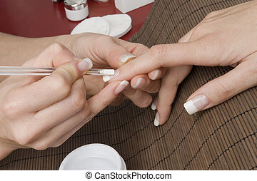 manicure - beautiful hand is getting a perfect manicure