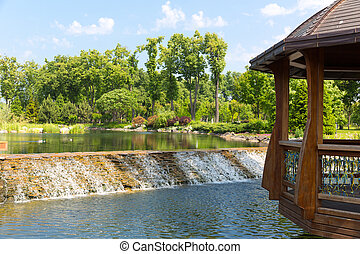Beautiful lake in green park with wooden summer-house