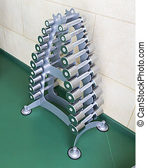 Set of dumb-bells on the stand in the gym