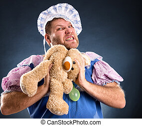 Spiteful man with teddy bear in studio