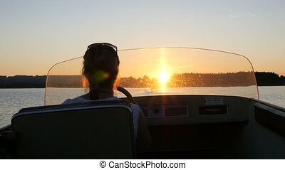 Motorboat Woman into sunset - Woman riding a motorboat into...