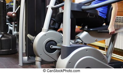 Girl in a fitness room on an exercise bike. - The girl goes...