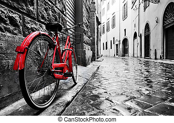 Retro vintage red bike on cobblestone street in the old...