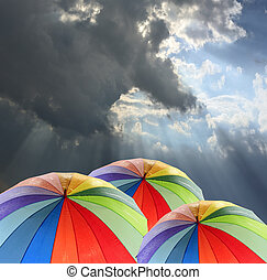 Rainbow umbrella against blue sky