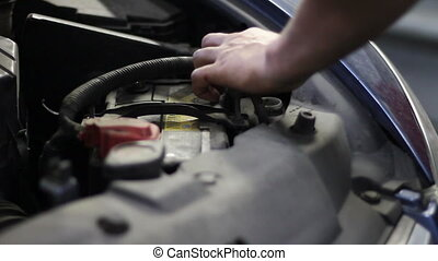 worker changing of antifreeze in car at service station -...
