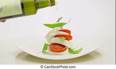 pouring olive oil with tomatos and mozzarella - pouring...