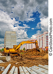 Excavator on the construction site beneath cloudy sky