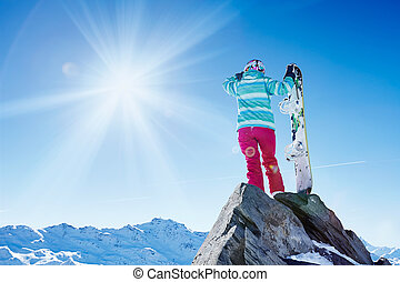 Snowboarder looking to mountains - Back view of female...