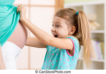 Little child girl looking at mother pregnant tummy