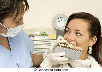 dentist is looking for the correct colour of the teeth