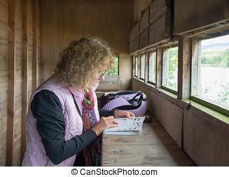 Female Bird Watcher identifying birds in a book