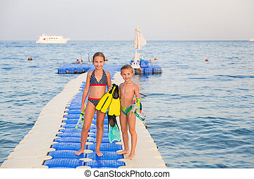 Cute girls with water masks and swim fins walking on pontoon...