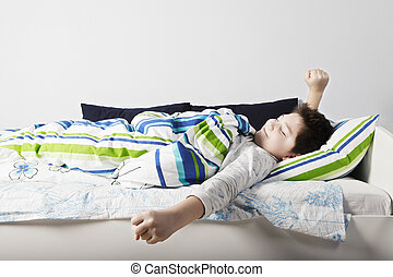 Wake up of contented caucasian boy laying down in bed at...