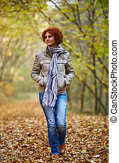 Woman having a walk in the woods - Redhead caucasian woman...