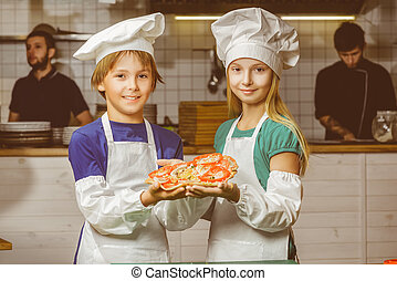 Funny happy chef boy and girl cooking at restaurant kitchen...