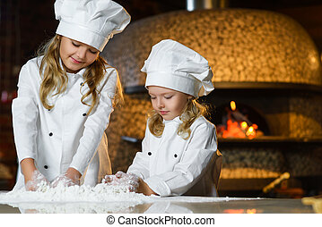 Funny happy chef boy width girl cooking at restaurant...