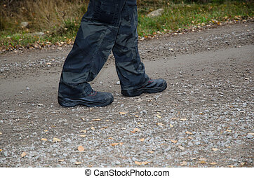 Walking on a gravel road - Walking with black boots and...