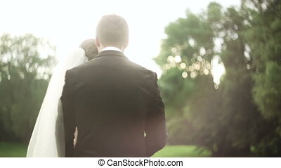 Bride groom holding hands at  sunset in the park