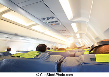 People in the plane - People are sitting on the seats in the...