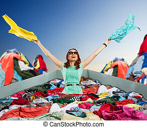 Happy woman sitting in clothes - Young happy woman in...